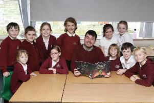 Ross Montgomery with some of the pupils with his new book