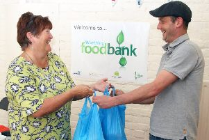 Aaron Payne collects his food parcel from Worthing Foodbank manager Julie Denyer. Photo by Derek Martin DM1942555a