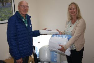 Littlehampton Rotary Club president Bruce Green hands over bedding and towels to Louise Gisbey, development and sustainability manager at Safe in Sussex