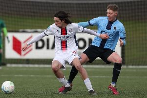 Coleraine's Jamie Glackin holds off Institute midfielder Evan Tweed.