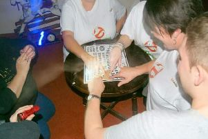 At a charity ghost hunt, the medium (left) asked her 'spirit guide' to lead the seance, Ellie said. The photograph seems to show a ghostly arm touching the ouija board.