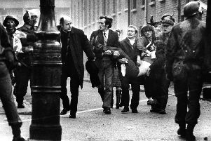 Bishop  Daly with a wounded man on Bloody Sunday. Picture: Pacemaker
