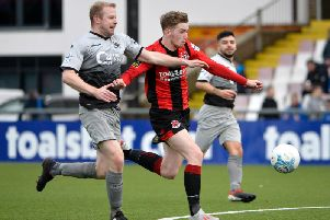 Crusaders Jamie McGonigle holds off Institute's Graham Crown before firing home their equaliser.