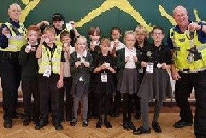 PCSO's and children holding the reflective badges. EMN-180312-151254001