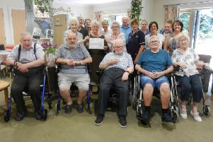 Staff and residents at Highdown Court in Worthing present a cheque to Maureen Johnson, sub branch organiser at Worthing and Washington Parkinson's UK