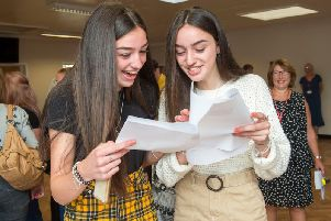Twin sisters, Ellie and Evie Odlin, open their results together.