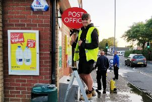 A worker installs the Post Office sign outside the Spar shop in Sutton on Sea. (Photo: Adrian Benjamin).