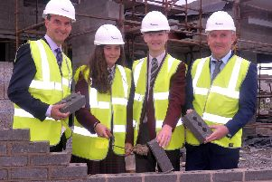 Pictured at a bricklaying ceremony at the new Clann Eireann Youth Centre are from left, Derek Baker, permanent secretary, Dept of Education, Grace Crosby and James Beatty, St Ronan's College students, and Dee McKerr, chairman of Clann Eireann Youth Development Committee. INLM42-206.