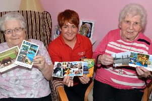 Kathy Davison, centre, personal activities leader at Mahon Hall Care Home pictured with residents, Sybil McCoo, left, and Norah Mulholland and some of the postcards received from all over the World after an online appeal by Kathy. INPT42-200.