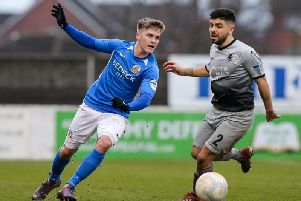 Glenavon's Josh Daniels skips away from Institute defender Ryan Morrow.