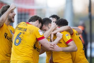 Andy Williams is mobbed by his team-mates after netting in injury-time at Stevenage