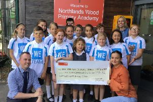 Mark Sears presenting the cheque to Natalie Hogben, with the school's WE Team, India and Mrs Cheesmur