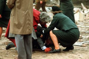 A police officer and a member of the public rush to assist one of the many people injured in the IRA's bomb attack on the Remembrance Day parade in Enniskillen in 1987 in which 12 people were killed. Nobody has ever been held accountable for the atrocity, Photo: Pacemaker