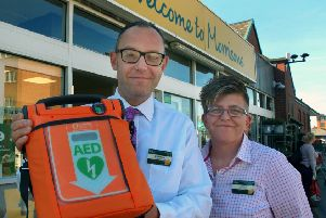 Matthew Griffiths, with Morrisons store manager Evette Ainley-Hall, holding the in-store defibrillator which he used to save a Melton customer's life EMN-180110-105102001