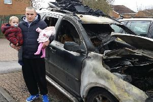 James Nairn, holding two of his young children, next to his car which was destroyed in an arson attack in Drummond Walk, Melton EMN-190402-141431001