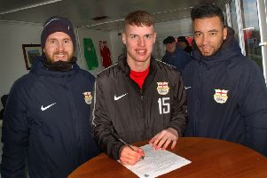 Kyle Reek signs on the dotted line with Melton Town co-manager Tom Manship (left) and Nathan Arnold EMN-190502-083438002