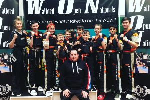 Andrew Hicks (front) with his team of fighters at the Watford Open. From the left are  Atlanta Hickman, Aaron Leonard, Lucy Hicks, Joshua Leonard, Oliver Profit, Denas Jankauskas, Tajus Jankauskas, Jolie Franks, Shiv Panchal and Aaron Dickerson.