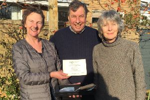 Rose Dejardin - who is stepping down after many years as county organiser - presenting, on behalf of the National Garden Scheme, an engraved trowel to David and Jeffy Wood who have opened their garden at Townsend House, Wing for ten years PHOTO: Supplied