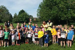 Runners from Melton's junior parkrun with two volunteers holding up the new AED EMN-190613-122008002