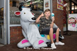 Laurence Robinson, nine, wins the competition to name the cow outside Gazzeria ice-cream restaurant in Meadow Walk, Buckingham - the winning name is 'Mary Moo'