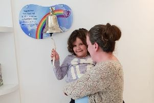 Evie Moore, with mum Helena Isaac, rings the bell at Sheffield Children's Hospital to celebrate being given the all-clear from leukaemia EMN-191021-150553001