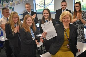 Long Field Academy assistant principal Sharon Maloney is congratulated for passing her GCSE in English language by students and the school's director of English studies, Rhea Fallows, who helped her study for it EMN-200127-130437001