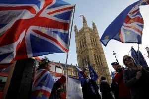 Anti-brexit campaigners wave Union and EU flags outside the Houses of Parliament