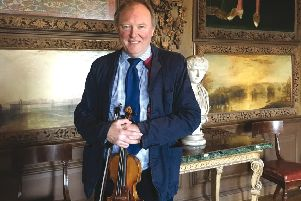 Sussex creative Andrew Bernardi with his Stradivarius violin beneath the Grinling Gibbons carved instruments at Petworth House which were both created c.1696. SUS-190128-113850001