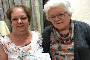 Broughshane WI treasurer Ann McMaster presents a cheque for �435 to Mary Knox BEM at the Institute's recent annual Quiz Night.