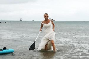 Dawn Winfield-Hunt paddleboarding in her wedding dress. Picture: Dawn Winfield-Hunt/PA Wire