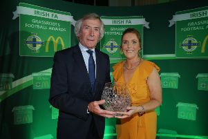 Mid-Ulster Ladies F.C. Chairperson, Elaine Junk, receives the Outstanding Contribution to Grassroots Football Award from  McDonald's Football Ambassador, Pat Jennings, at Belfast City Hall.