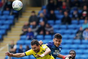 Ryan Tafazolli (blue) seen here in action against Oxford earlier this season is on the substitutes' bench.