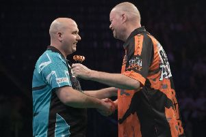 Rob Cross (left) shakes hands with opponent Raymond van Barneveld in Nottingham tonight. Picture courtesy Lawrence Lustig/PDC