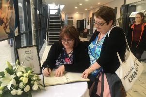 Marie O'Neill (right) and her friend, Siobhan, sign the Cookstown book of condolence for the families of three teenagers who died on Sunday