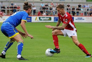 Brackley Town's Carl Baker takes on  FC v Alfreton Town's Dale Witham in Saturday's opener. Photo: Jake McNulty
