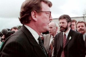 "David Trimble and Gerry Adams pass each other during the 1998 Stormont talks. David Barbour says: ""I remember David Trimble saying 'Lets go and test them on this' So he jumped, calling on Gerry Adams to follow. It seemed Gerry was behind looking for a parachute"""