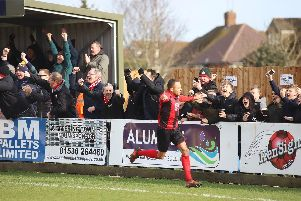 Rhys Hoenes heads off to celebrate, much to the delight of the Kettering Town fans, after he opened the scoring in the 3-0 win over Banbury United. Pictures by Peter Short