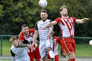 Bexhill United captain Craig McFarlane wins a header during Saturday's 2-2 draw away to Steyning Town. Picture by Stephen Goodger