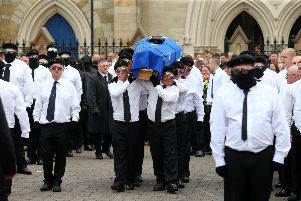 A crowd of men with their faces covered and wearing berets led the funeral procession to St Peter's Cathedral for the funeral of Martin McElkerney