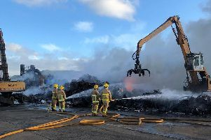 Fire crews, assisted by McKenzies crane drivers, dampen down the smouldering pile of scrap metal. Pic: McKenzies (NI) Ltd