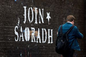 "A man walks past graffiti in the North Belfast area with the writing ""Join Saoradh"", an unregistered far-left political party formed by dissident republicans. Photo credit: Liam McBurney/PA Wire"