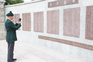 Ex Serviceman David Baird takes a picture of the new memorial wall.