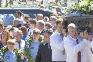 """The remains of the late rally driver Manus """"Mandy"""" Kelly are carried his resting place in Conwal graveyard in Donegal as his sons wear garlands from his wins in the Donegal International Rally. Press Association picture"""