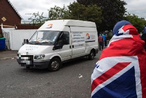 A woman wrapped in a Union flag watches a van carrying tyres that were removed from the 11th night bonfire that was erected at Avoniel Leisure Centre.(Photo: Liam McBurney/P.A. Wire)