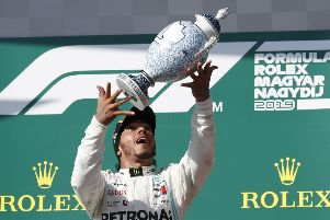 Mercedes driver Lewis Hamilton of Britain celebrates on the podium after winning the Hungarian Formula One Grand Prix at the Hungaroring racetrack. (AP Photo/Laszlo Balogh)