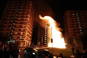 Crowds watch as a bonfire is lit in the New Lodge area of Belfast on Thursday night