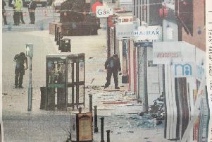 'BOMB TERROR: Police sit through the debris at cordoned-off London Road after the blast
