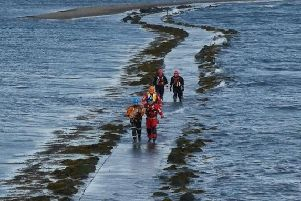 Coastguard rescue team members carry the puppy to safety. Pic shared on the CGOC Belfast Coastguard Facebook page