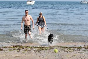 Stephen Currie and Emma Sharkey from Belfast with their dog Marley at Helens Bay over the BAnk Holiday weekend. 'Photograph by Declan Roughan