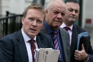 Victims campaigner Raymond McCord (centre) and solicitors Ciaran O'Hare (left) and Paul Farrell outside the Royal Courts of Justice, Belfast